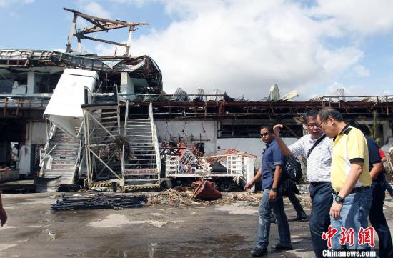"""11月10日,菲律宾总统阿基诺前往遭超强台风""""海燕""""袭击的重灾区视察灾情。图为阿基诺在内政部长罗哈斯等官员陪同下视察重灾区塔克洛班市。中新社发 Malacanang 摄"""