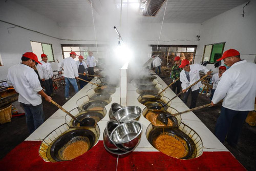 10月31日,义乌市义亭镇小宝红糖厂内,工人们在熬着热气腾腾的糖水。新华社记者 徐昱 摄