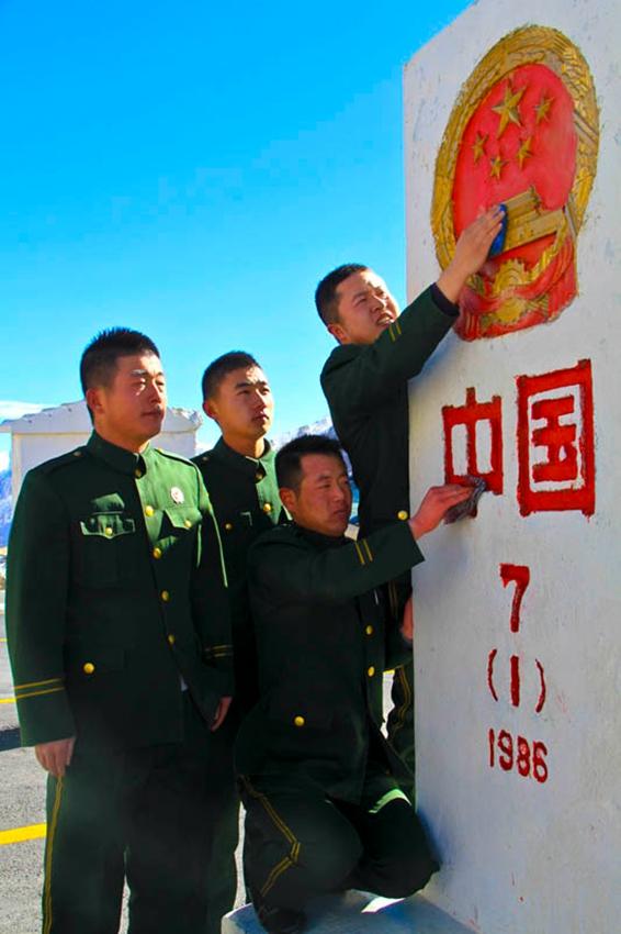 11月11日,退伍老兵擦拭界碑,依依惜别。