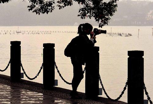 11月4日,一位摄影爱好者倚在西湖岸边的石栏杆上进行创作。新华社记者王颂摄
