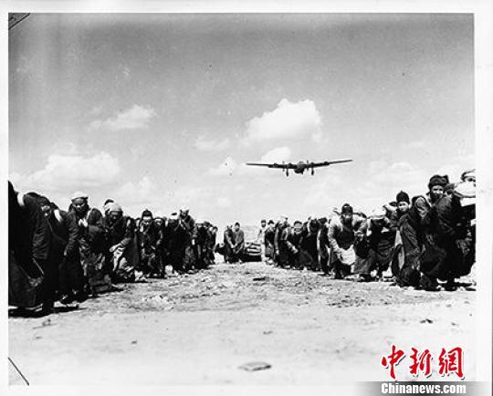 1944年3月31日,照片所示体现了现代机械与传统民工的强烈对比,表现这群中国民工奋力拖拉一个巨石碾子滚过跑道,用血肉之躯修建机场铺筑通往民族解放之路。 资料图 摄