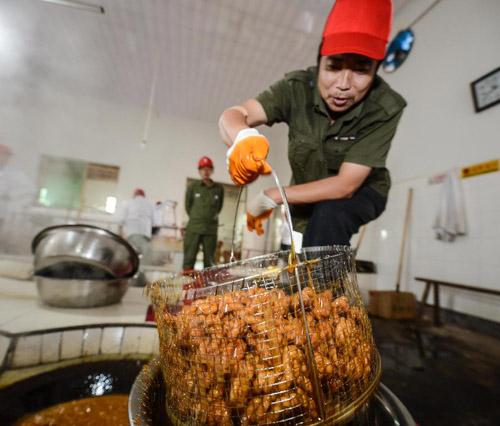 10月31日,义乌市义亭镇小宝红糖厂内,一名工人把一篮麻花放入浓稠的糖水中。新华社记者 徐昱 摄