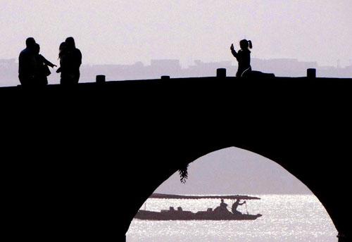 11月4日,游客在西湖景区的断桥上赏景、拍照。生活在杭州的人是幸福的,因为杭州有西湖。新华社记者王颂摄