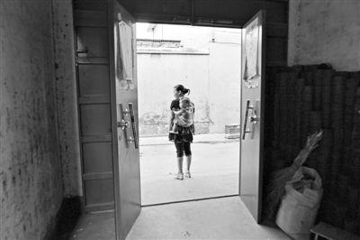 2013年8月8日,嫁到中国农村的越南新娘何氏欢带着孩子在家门口玩。新京报记者 秦斌 摄