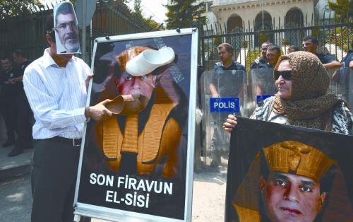 13日,支持穆尔西的土耳其示威者在埃及驻土使馆外抗议。他们用鞋拍打埃及军方领导人塞西将军的法老像。