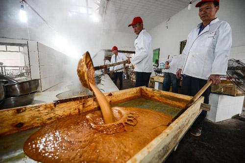 10月31日,义乌市义亭镇小宝红糖厂内,工人们把甘蔗榨出来的糖蔗水经过数口铁锅层层加热成的糖稀,倒入木盆晾干。新华社记者 徐昱 摄