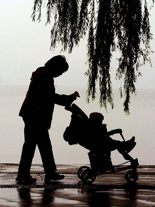 11月4日,一位市民推着童车在西湖岸边游玩。