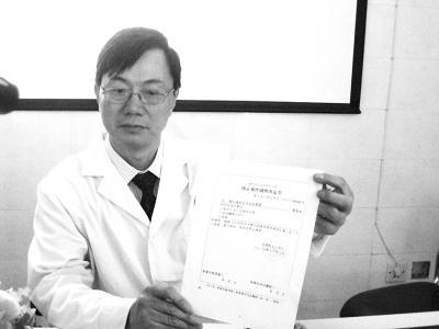 图为肖传国拿着深圳市公安局龙岗分局出具的终止案件调查决定书。