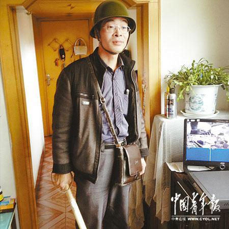 柯尊年举报副县长公款出国旅游后,出门总是头戴钢盔。本报记者 刘星摄