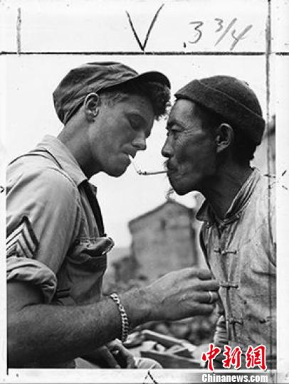 1944年10月14日,一位年长的中国男人在满目疮痍的云南那腾冲街头停下来,向一名美军军士借火,点燃他的烟锅。 资料图 摄