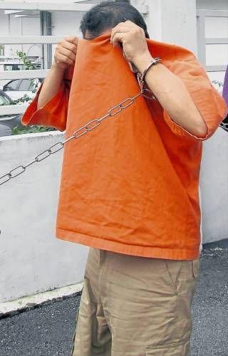 嫌犯被带往法庭延扣时,以上衣遮脸掩盖面目。(《南洋商报》)