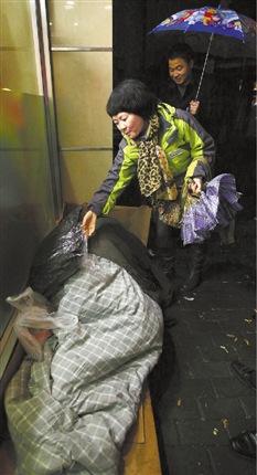 龙翔桥附近,流浪者在睡觉,工作人员给了他一件棉衣