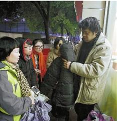 流浪者老吴接过救助站工作人员送的棉衣