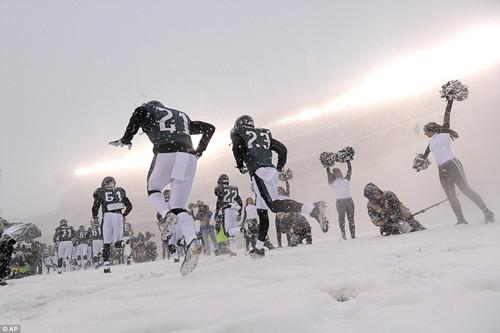 费城老鹰队队员迈过被雪掩埋的场地出场。天气太冷,啦啦队员也不得不裹上厚厚一层。