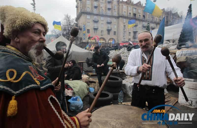 当地时间2013年12月21日,乌克兰基辅,示威民众在击鼓呐喊。(图片来源:东方IC)