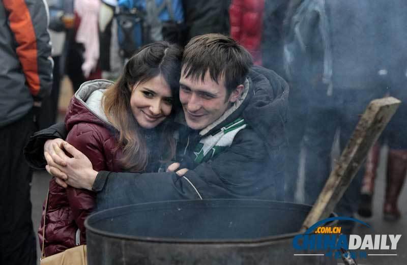 当地时间2013年12月21日,乌克兰基辅,示威民众在火炉边取暖。(图片来源:东方IC)