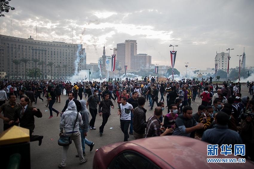 12月1日,在埃及首都開羅解放廣場,示威者在催淚瓦斯的煙霧中繼續游行示威。新華社記者 許楊攝