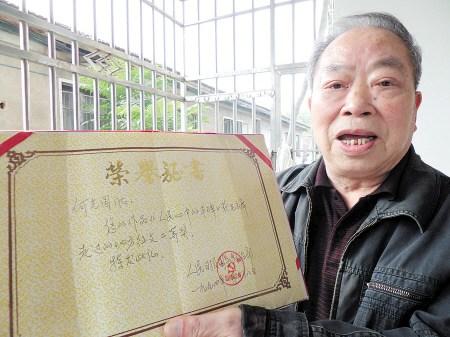 """1993年,何光国将""""毛主席来到龙凤山""""这一幕,以《人民心中的丰碑》为题,写成回忆文章,参加《人民日报》举办的征文活动,荣获二等奖。贺文兵 摄"""