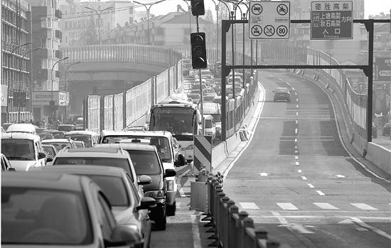德胜高架保俶北路下匝口的汽车排起长队。 本报记者 林云龙 摄