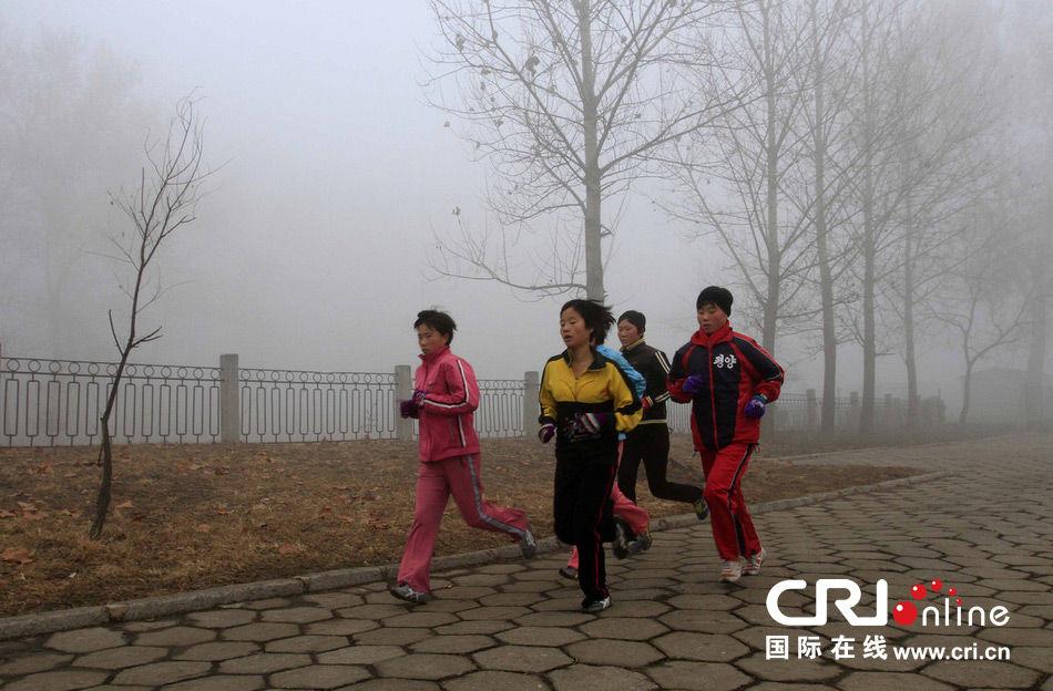 当地时间2013年10月4日,朝鲜平壤运动员在晨雾中训练。 图片来源:Kim Kwang Hyon/东方IC
