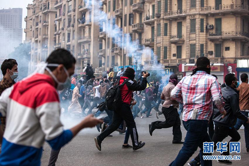 12月1日,在埃及首都開羅解放廣場,示威者在催淚瓦斯的煙霧中四散奔逃。新華社記者 崔新鈺攝