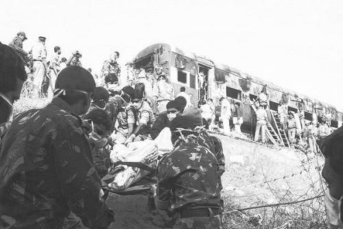 图片说明:搜救人员从车厢里抬出遇难者遗体。
