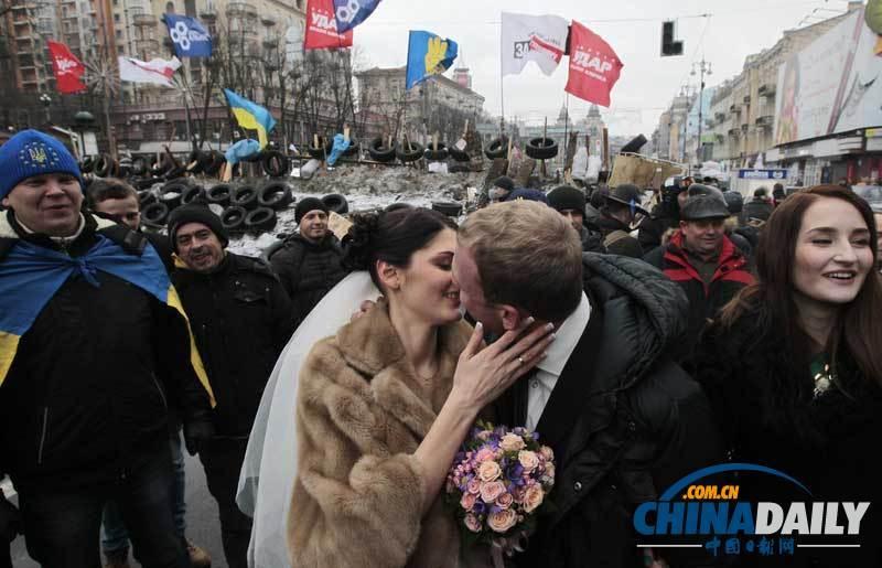 当地时间2013年12月21日,乌克兰基辅,一对新人在独立广场的示威人群中成婚。(图片来源:东方IC)