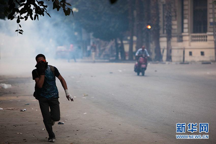 12月1日,在埃及首都開羅解放廣場,一名示威者在催淚瓦斯的煙霧中奔跑離開現場。新華社記者 崔新鈺攝