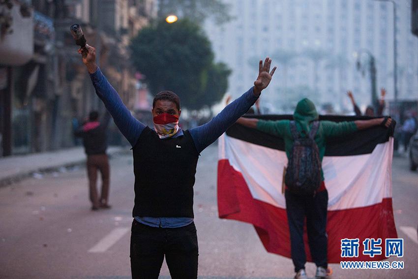 12月1日,在埃及首都開羅解放廣場,示威者在催淚瓦斯的煙霧中繼續游行示威。新華社記者 崔新鈺攝