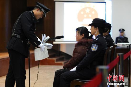 2013年12月30日,备受社会关注的陕西富平产科医生张淑侠拐卖婴儿案,在陕西渭南市中级人民法院公开审理。经过约8小时的庭审,法庭宣布择期宣判。图为法警正在让张淑侠确认证据。张远 摄