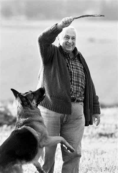 2001年1月20日,以色列南部,当时为总理候选人的沙龙在自家农场与家犬嬉戏。资料图片
