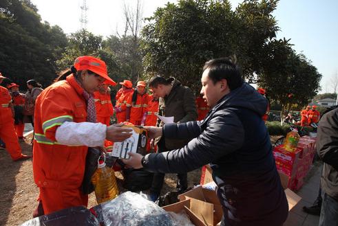 """年货分发现场。21日,杭州市拱墅近400名环卫工领到了公司派发给他们的""""温暖年货""""——保温饭桶、羽绒保暖内衣、保暖雨鞋等冬季御寒品。"""