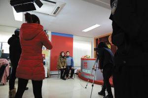 民政局工作人员在帮童某和陈某拍照。孙乔 摄
