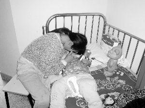 妈妈守着烁烁,不时亲吻安抚他 本组摄影 现代快报记者 陆文杰