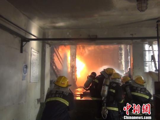 消防人员在扑灭明火 黄恩来 摄