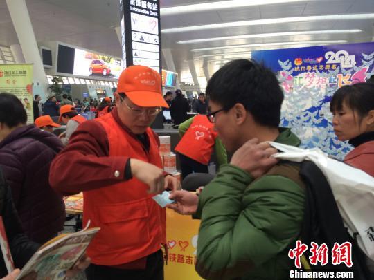 图为:志愿者为旅客解疑答惑。 张骏 摄