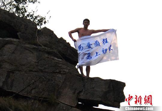 """爬上峰顶后,李童星打出""""为爱疯狂、马上裸攀""""的旗帜。 张明涛 摄"""