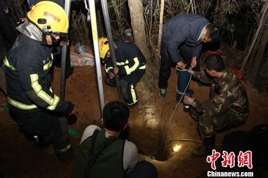 图为救援人员在盗洞上方观察情况。 沈燕斌 摄