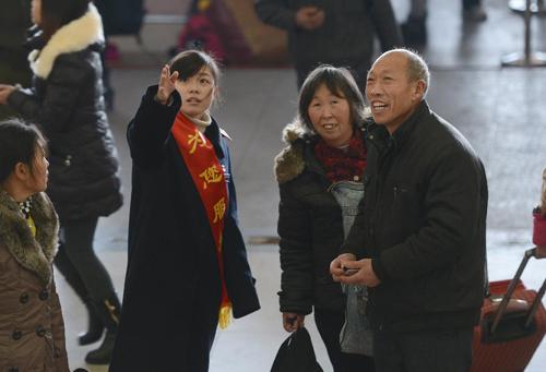 1月23日,义乌火车站一名工作人员在引导旅客候车。