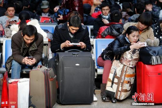 """1月25日,北京南站,候车的乘客看手机""""消磨时间""""。中新社发 盛佳鹏 摄"""