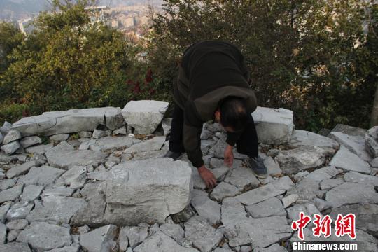 图为老人在整理一处松动的石头 朱柳融 摄