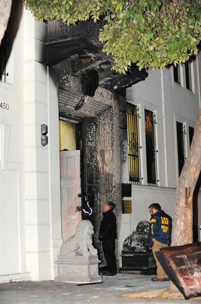 美国联邦调查局的探员在被烧毁的中国领事馆大门前调查取证。 陈钢 摄