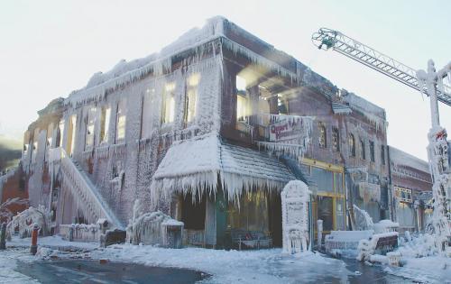美国中东部地区连日遭受暴风雪袭击。图为美国普拉茨茅斯一处失火大楼在消防水枪喷洒后结上厚冰。