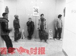 昨天,火车东站候车大厅的洗手间走廊里,乘客站在垃圾桶边上抽烟。