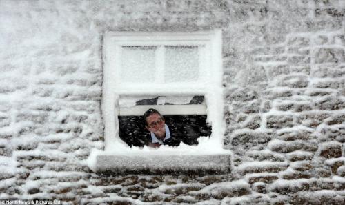 白雪覆盖房屋,民众探头观看窗外雪景。