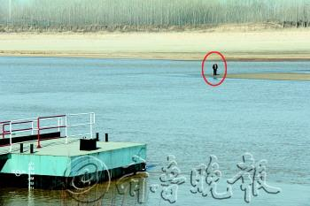站在黄河浅滩上的跳河男子。