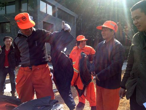"""在年货分发现场,一位环卫工在试穿保暖羽绒衣。21日,杭州市拱墅近400名环卫工领到了公司派发给他们的""""温暖年货""""——保温饭桶、羽绒保暖内衣、保暖雨鞋等冬季御寒品。"""